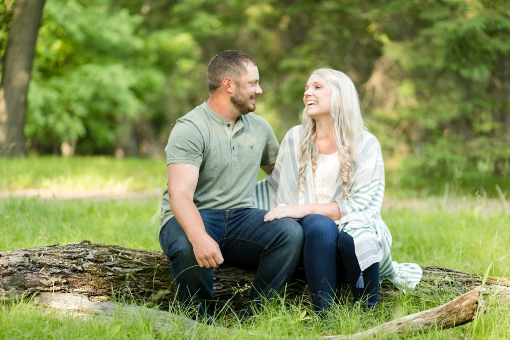 couple sitting on a log at Brunet Island State Park in Cornell, WI
