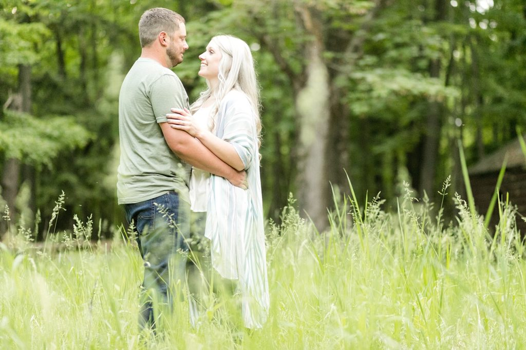 couple smiling at each other in a field at Brunet Island State Park in Cornell, WI