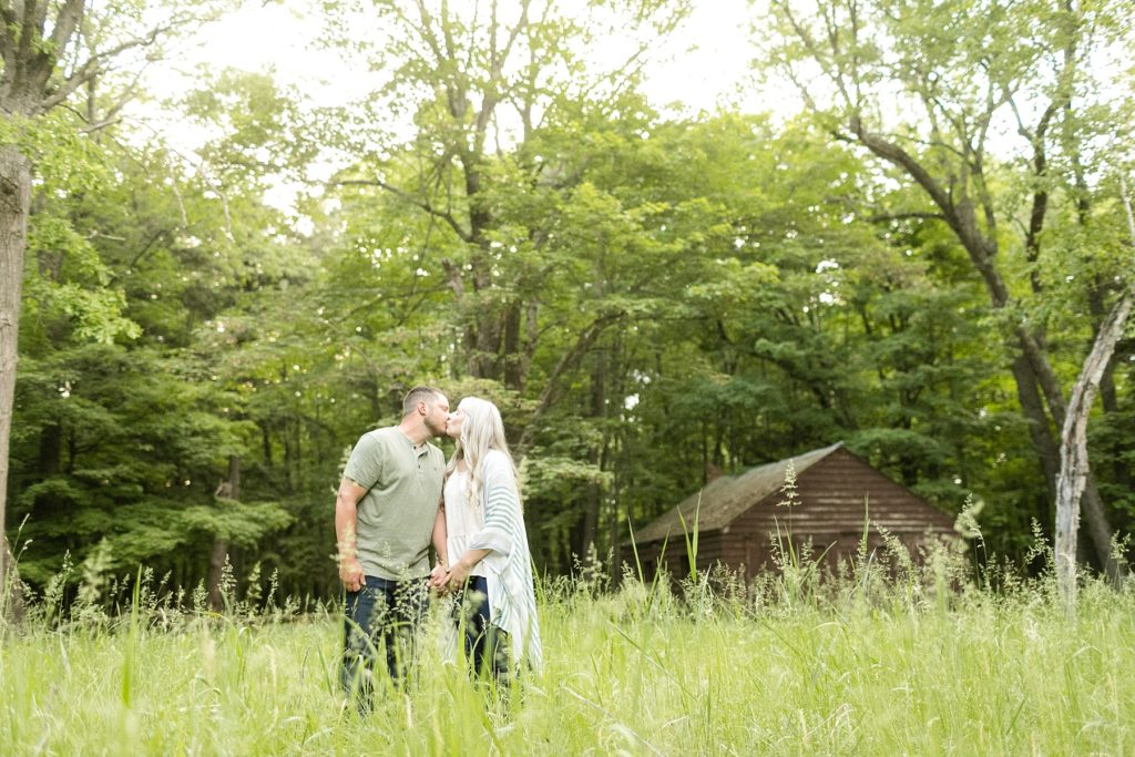 couple in a field with a cabin behind them at Brunet Island State Park in Cornell, WI