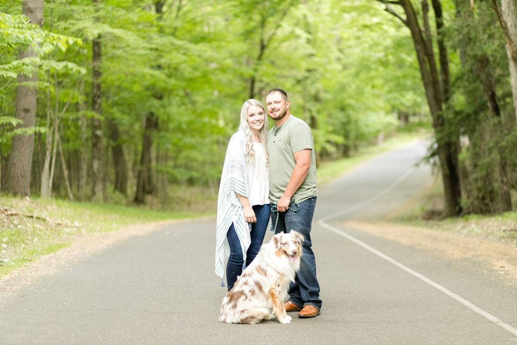 couple with their dog on a road at their engagement session at Brunet Island State Park in Cornell, WI