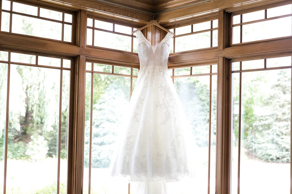 bride's gown hanging near windows at The Florian Gardens in Eau Claire, WI