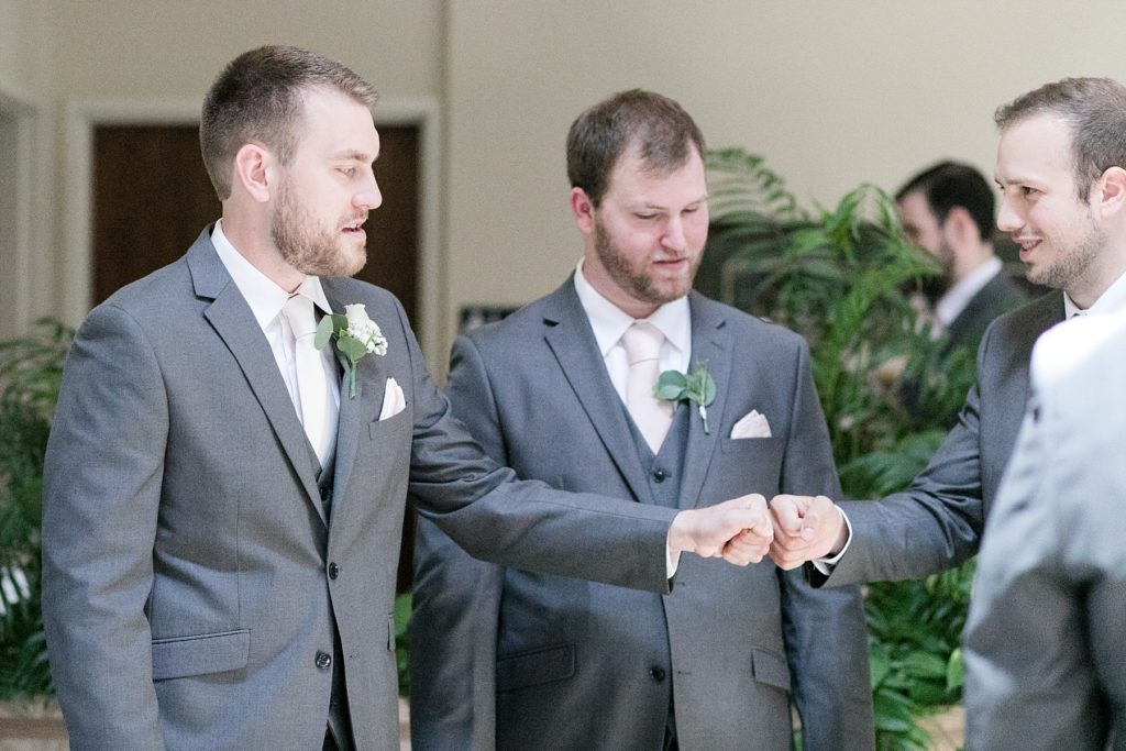 groom and best man fist bump before the ceremony at The Florian Gardens in Eau Claire, WI