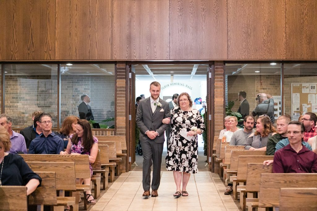 grooms mom walking groom down the aisle at Hope Lutheran Church in Eau Claire