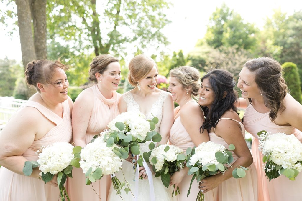 bridesmaids laughing with bride in the center at wedding atThe Florian Gardens in Eau Claire