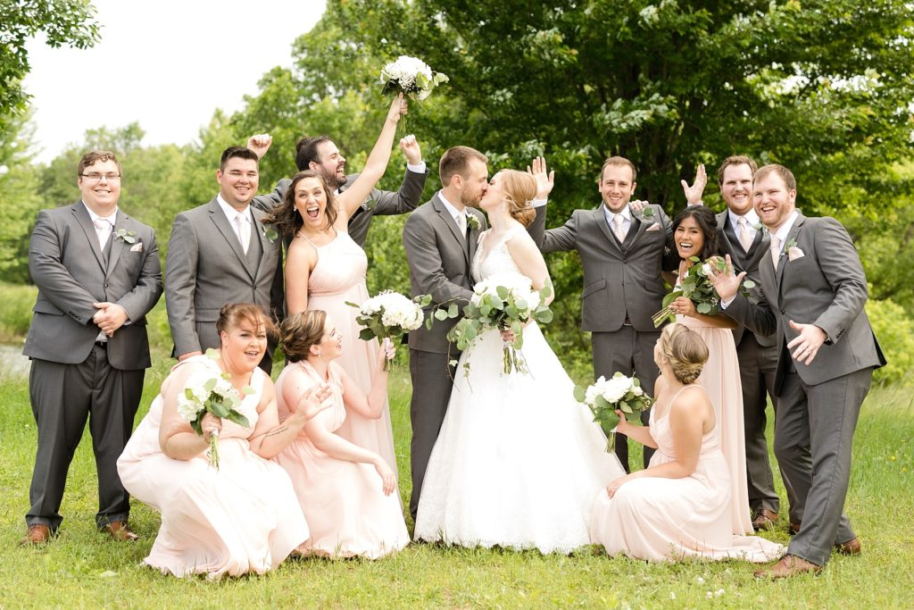 bridal party cheering while bride and groom kiss at wedding atThe Florian Gardens in Eau Claire