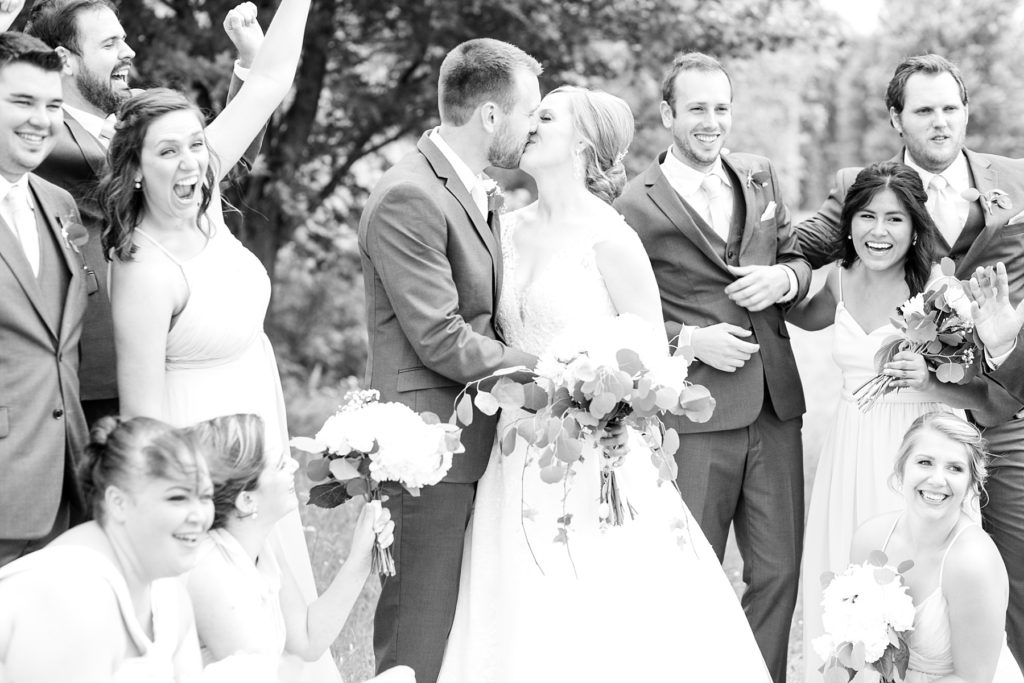black and white photo of bride and groom kissing with bridal party cheering at wedding atThe Florian Gardens in Eau Claire