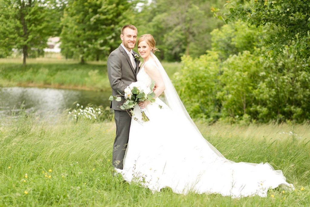 bride and groom infront of a lake at wedding atThe Florian Gardens in Eau Claire