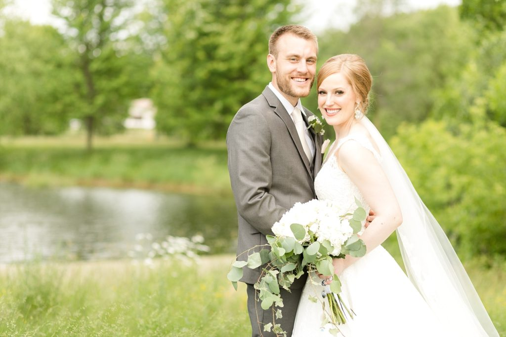 bride and groom smiling at the camera infront of a lake at wedding atThe Florian Gardens in Eau Claire
