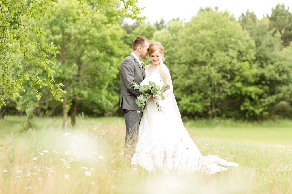 bride and groom in daisy field at wedding atThe Florian Gardens in Eau Claire
