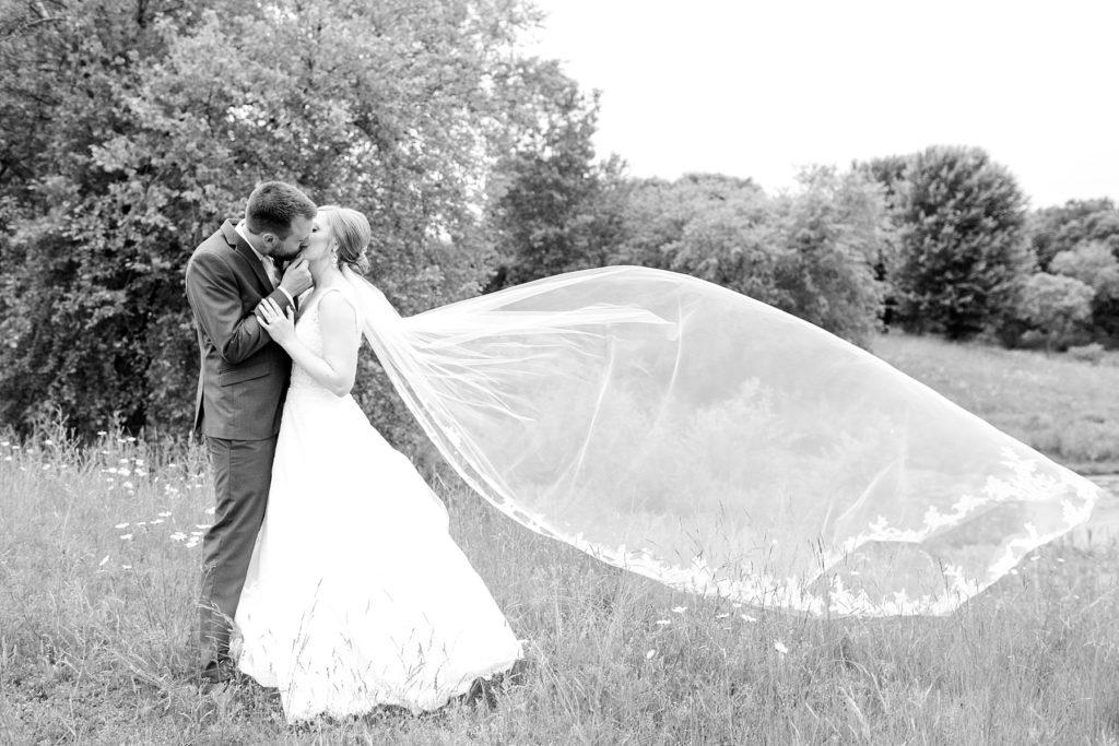 couple with cathedral length veil blowing in the wind at wedding atThe Florian Gardens in Eau Claire