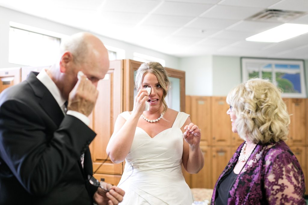 bride and father wipe tears from their eyes while mom smiles at the Eau Claire Golf & Country Club