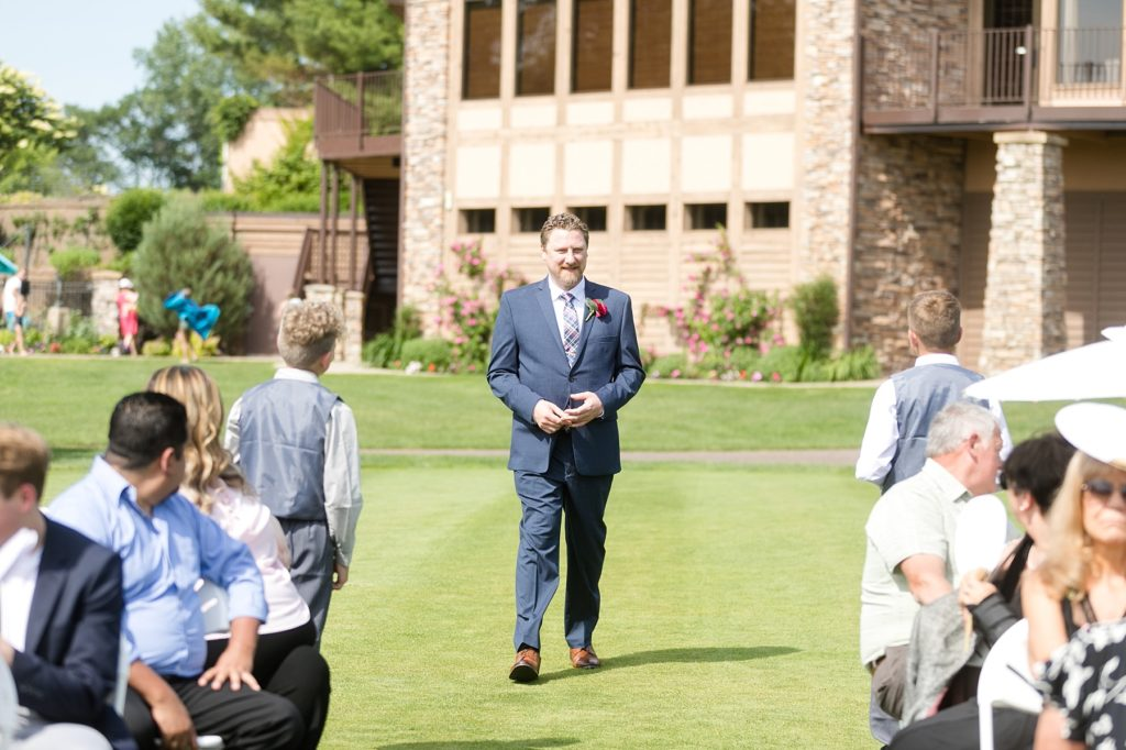 groom walking down the aisle in a navy suit at the Eau Claire Golf & Country Club