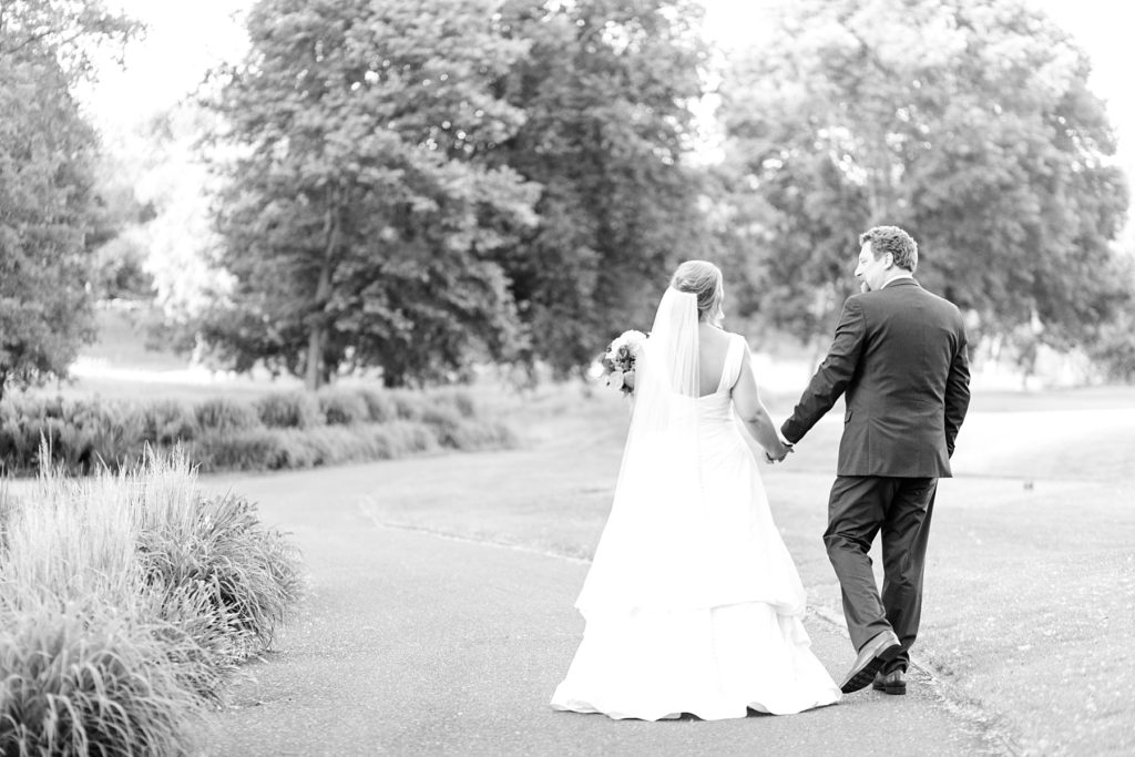 couple in black and white photo walking away from camera at the Eau Claire Golf & Country Club