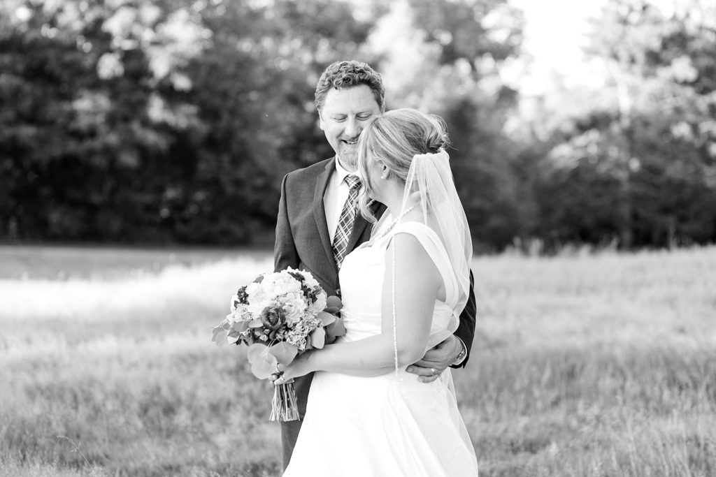 groom smiling at the bride in a black and white photo at the Eau Claire Golf & Country Club
