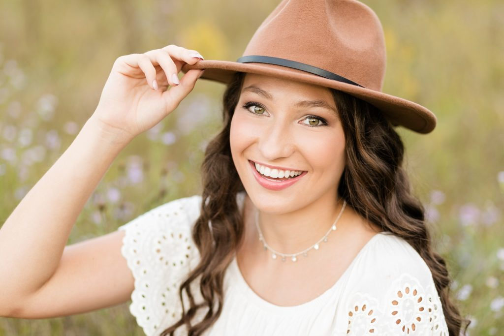Cadott high school senior Tabitha smiles at the camera with a hat on in a field of flowers.