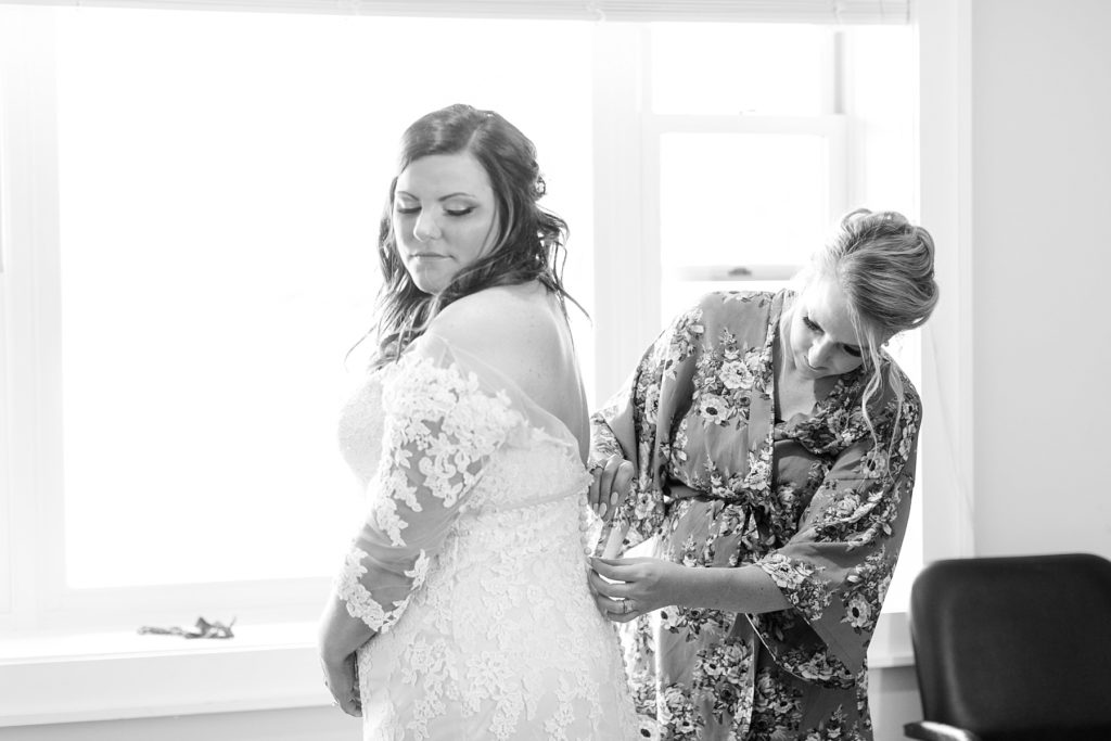 maid of honor buttoning bride into her lace gown on her wedding day at Lake Wissota Golf & Events