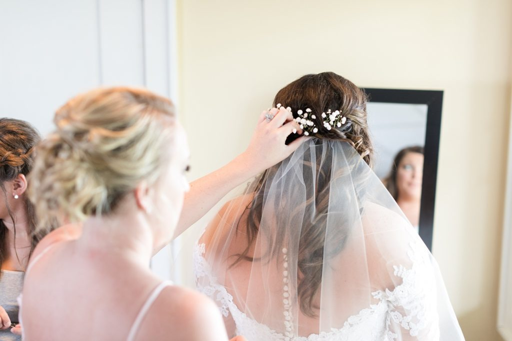 maid of honor placing the veil in the brides hair at Lake Wissota Golf & Events
