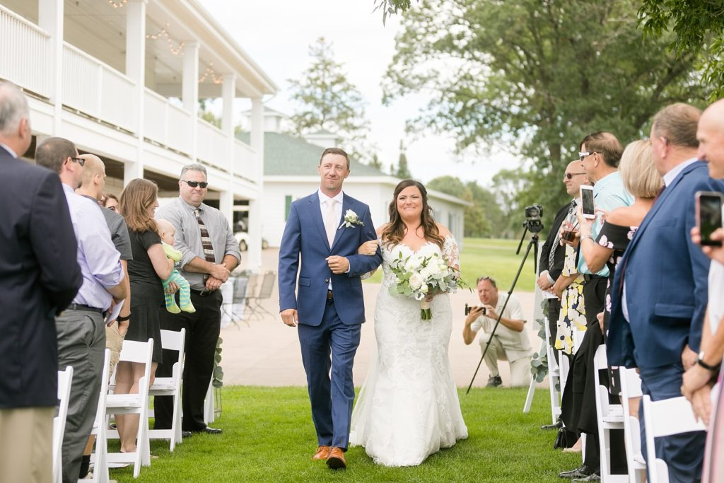 bride walking down the aisle with her brother outside by the lake at Lake Wissota Golf & Events