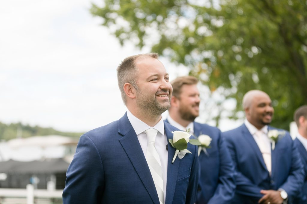 groom seeing the bride walking down the aisle for the first time at Lake Wissota Golf & Events
