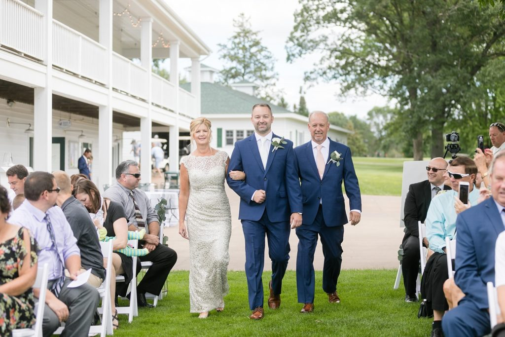 groom walking down the aisle with his mom and dad at Lake Wissota Golf & Events