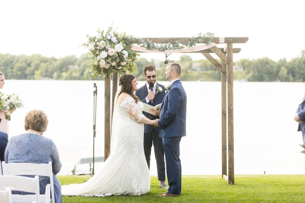 couple holding hands on the lawn at their wedding ceremony at Lake Wissota Golf & Events