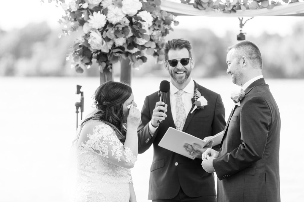 bride wiping her tears while the groom says his vows at Lake Wissota Golf & Events