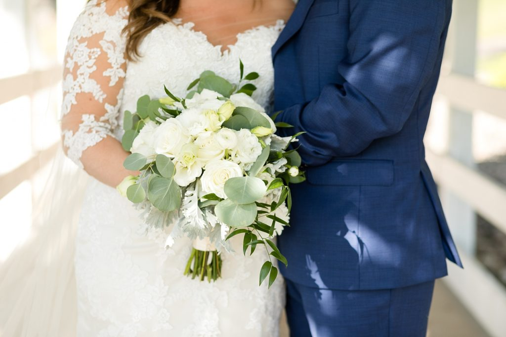 bride and groom holding a white and green wedding bouquet by Brent Douglas Flowers at Lake Wissota Golf & Events