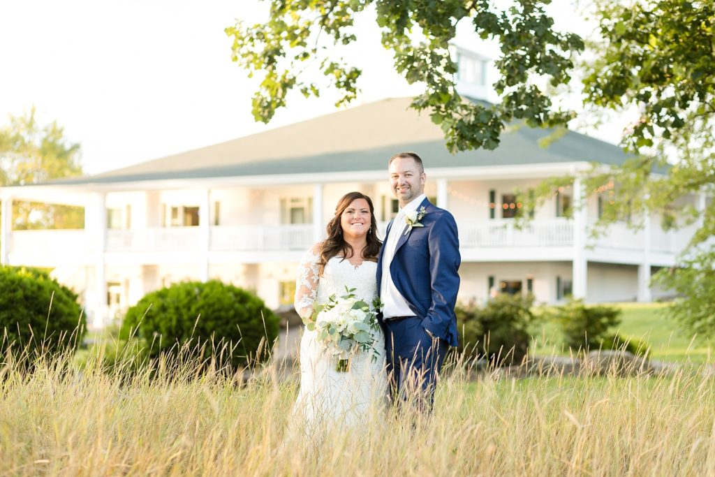 couple standing in tall grass infront of the building at Lake Wissota Golf & Events