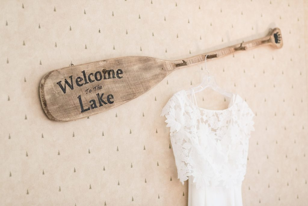 "brides dress hanging from a canoe paddle that reads ""welcome to the lake"" at The Beacons of Minocqua on their wedding day"