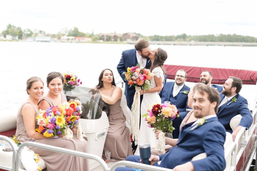 bride and groom with bridal party on a pontoon kissing on the lake at The Beacons of Minocqua on their wedding day