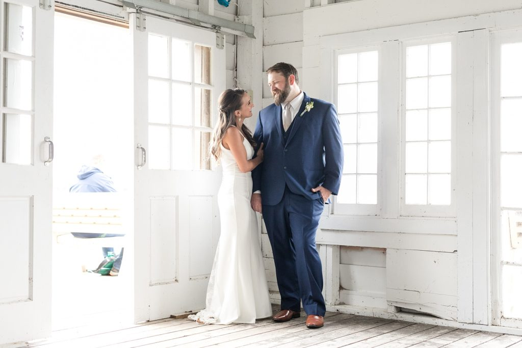 bride and groom in a white boathouse at The Beacons of Minocqua on their wedding day