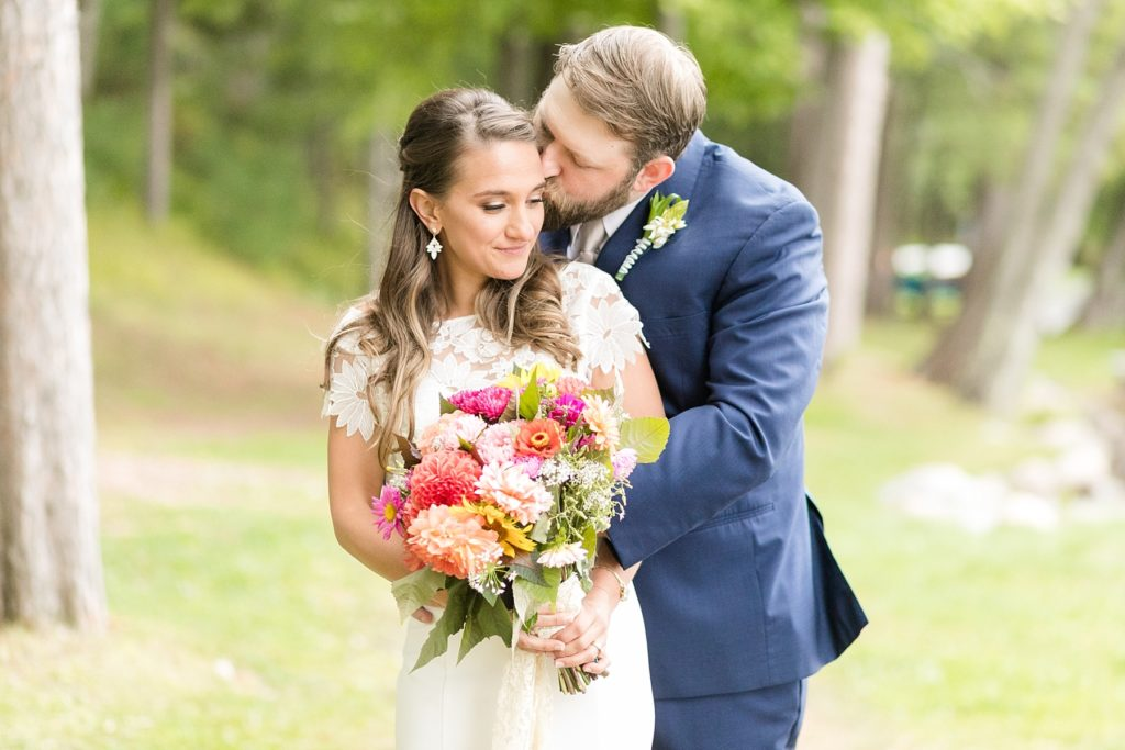 groom kissing brides cheek outside with a bright bouquet at The Beacons of Minocqua on their wedding day
