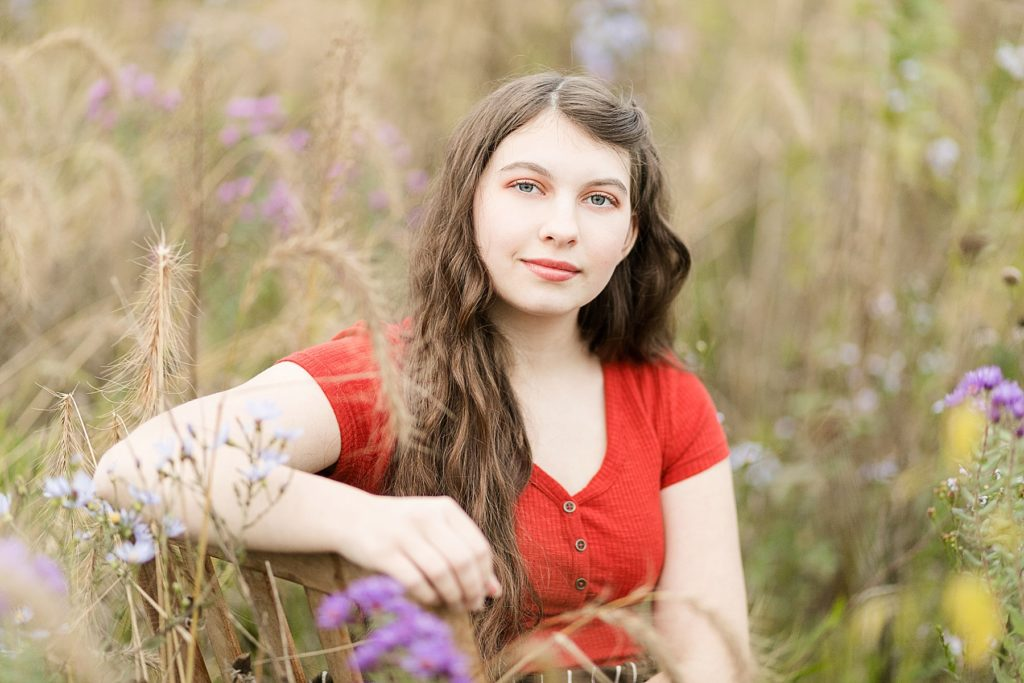 girl sits in field of flowers for her Cadott High School senior photos