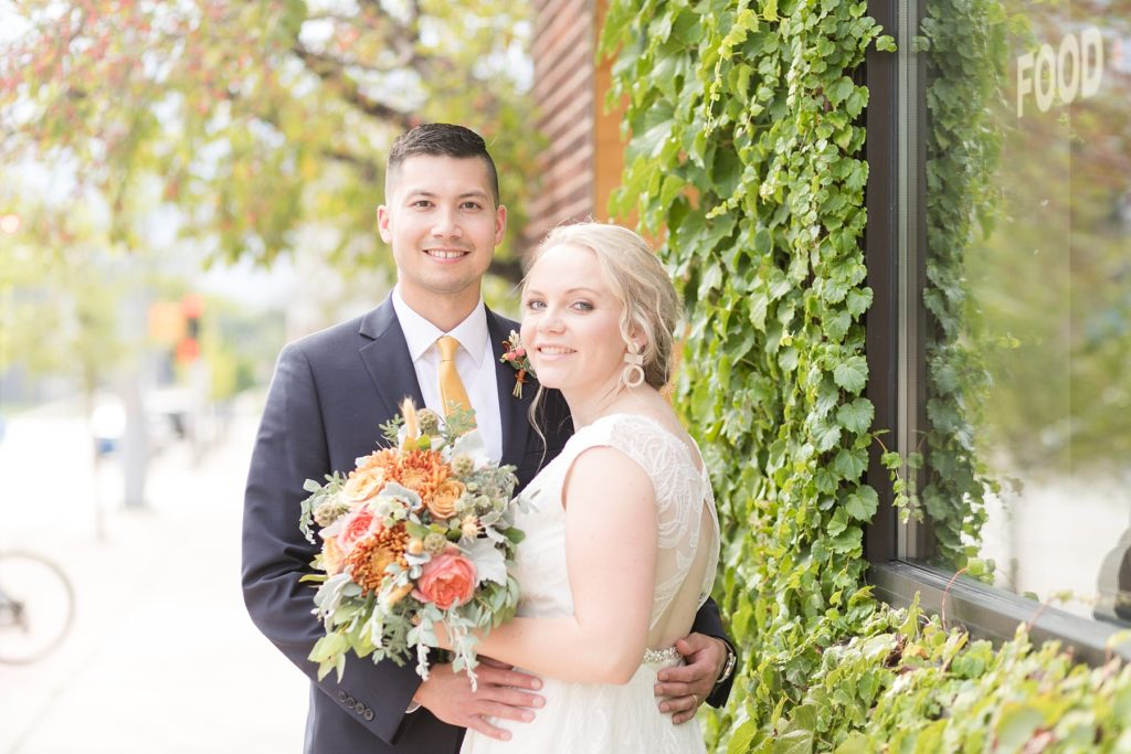 couple by the vine covered wall after getting married at The Oxbow Hotel in Eau Claire WI