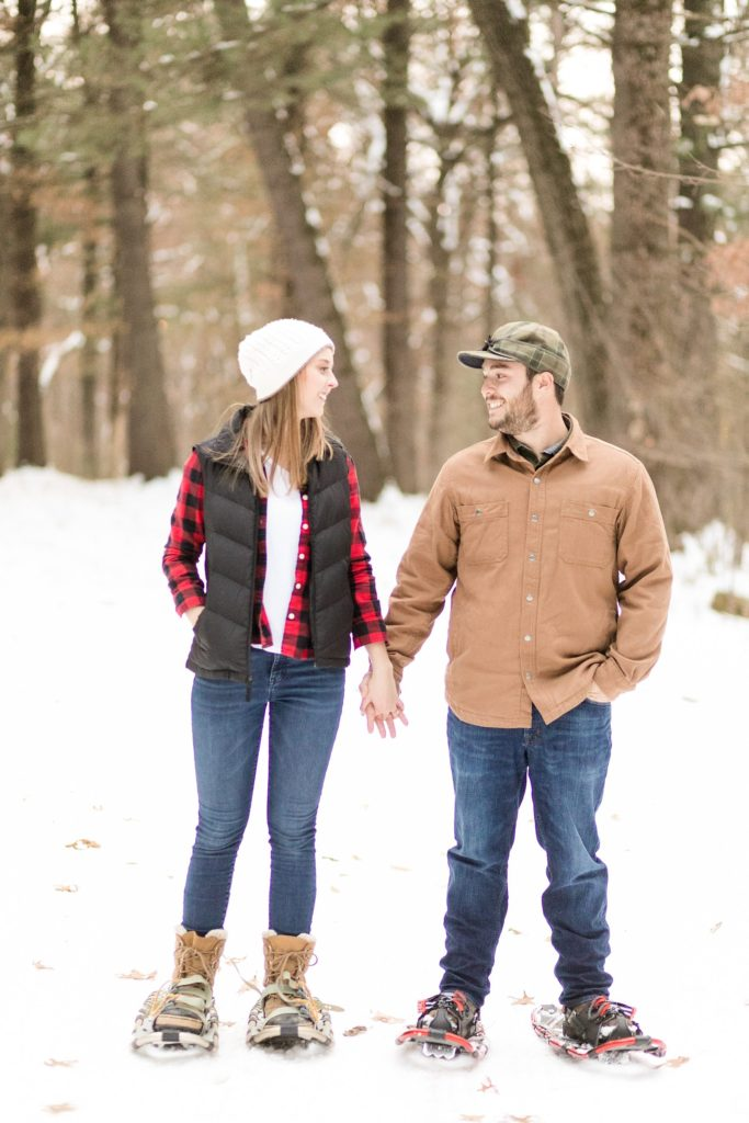 couple snowshoeing for their Wisconsin engagement photos