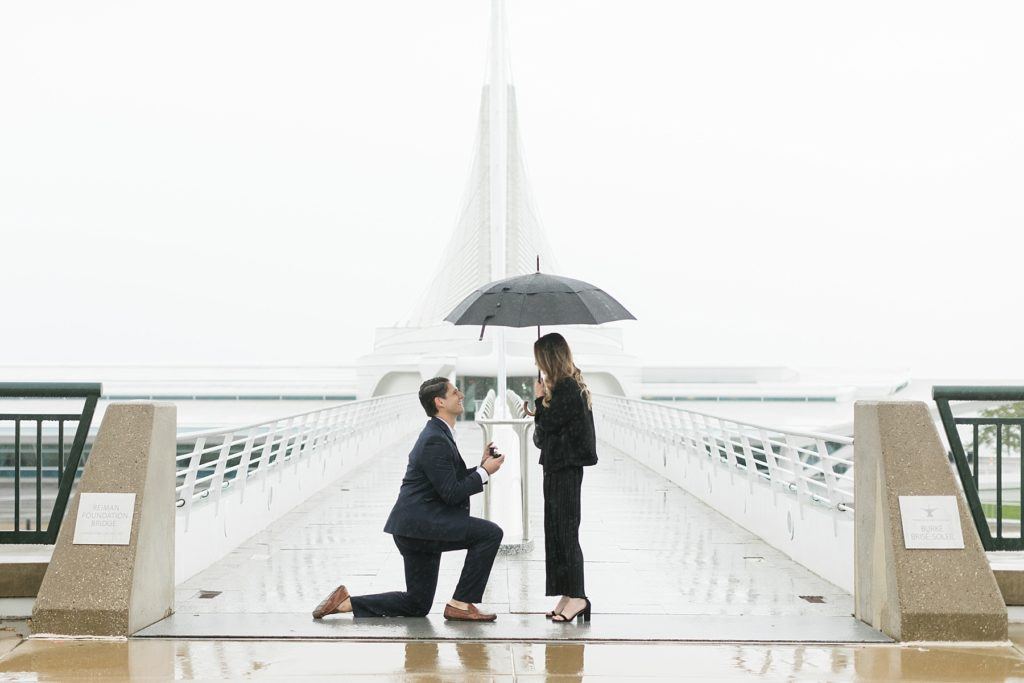 guy down on his knees in the rain at the Milwaukee Art Museum proposing on the bridge