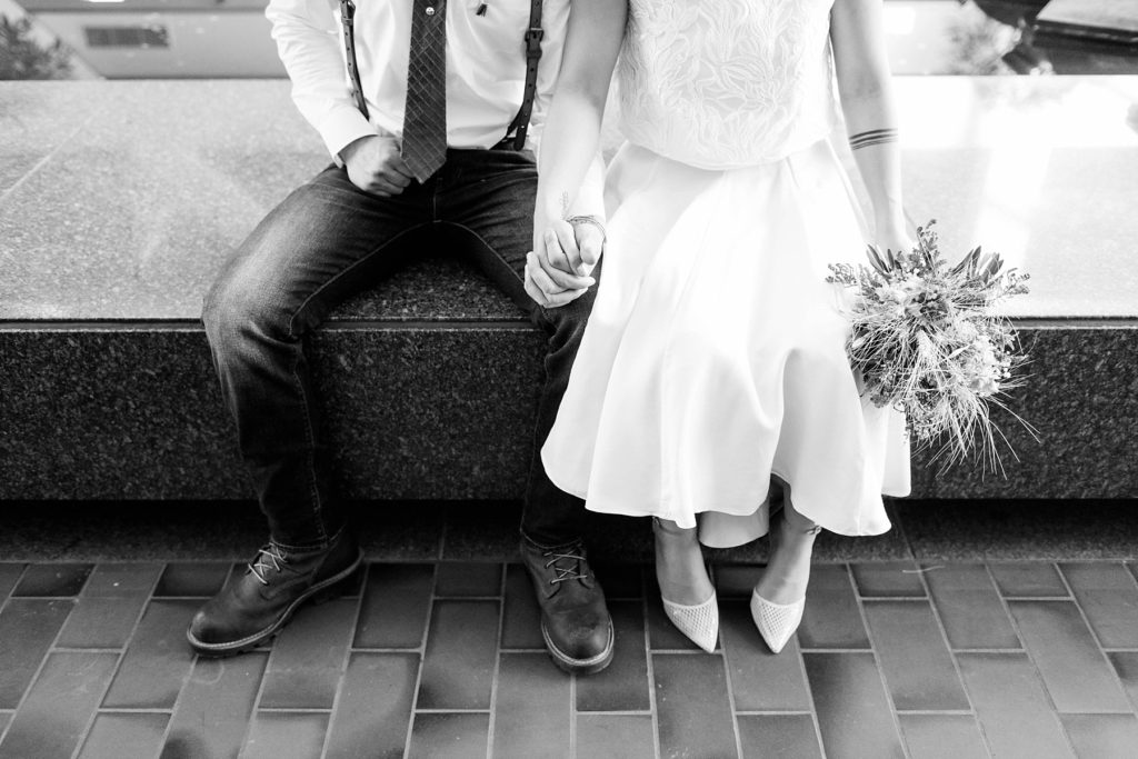 couple sitting in the atrium by the pools at the Hennepin County Government Center after having their Minneapolis courthouse wedding