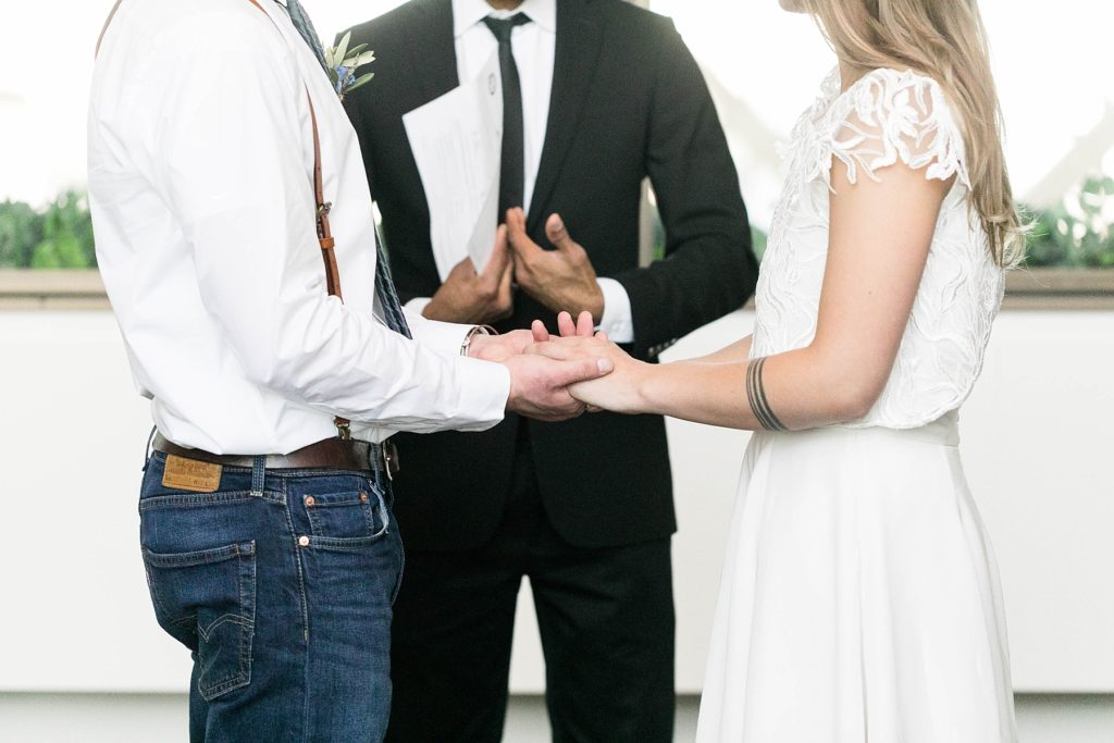 couple holding hands during their ceremony at the Hennepin County Government Center after having their Minneapolis courthouse wedding
