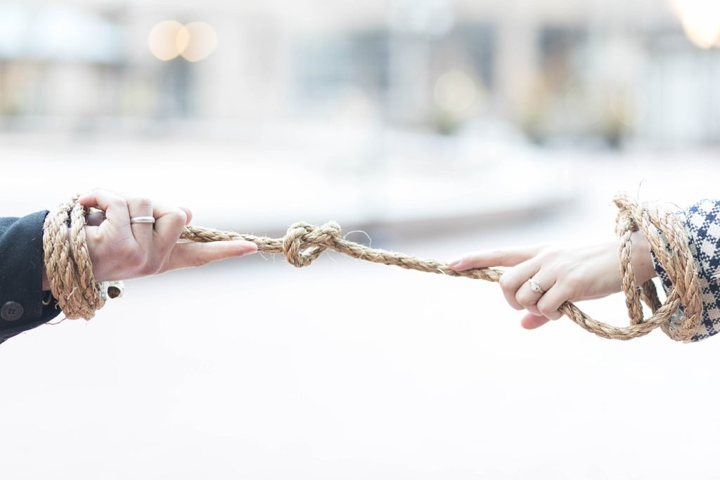 couple holding rope with new wedding rings at the Hennepin County Government Center after having their Minneapolis courthouse wedding