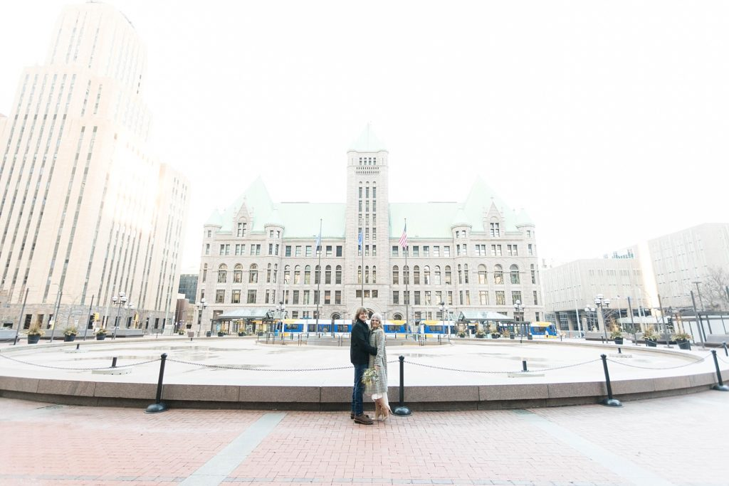 couple with the old city hall behind them at the Hennepin County Government Center after having their Minneapolis courthouse wedding