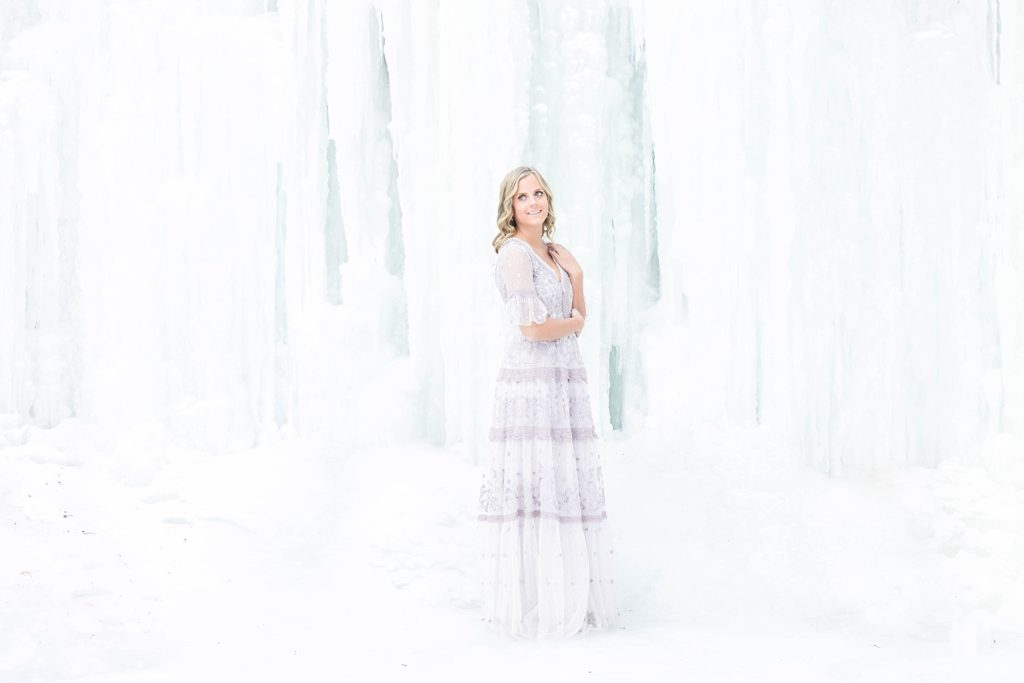 girl in Thread & Needle dress posing infront of an ice formation in Wisconsin for the Sisterhood of the Traveling Dress shoots.
