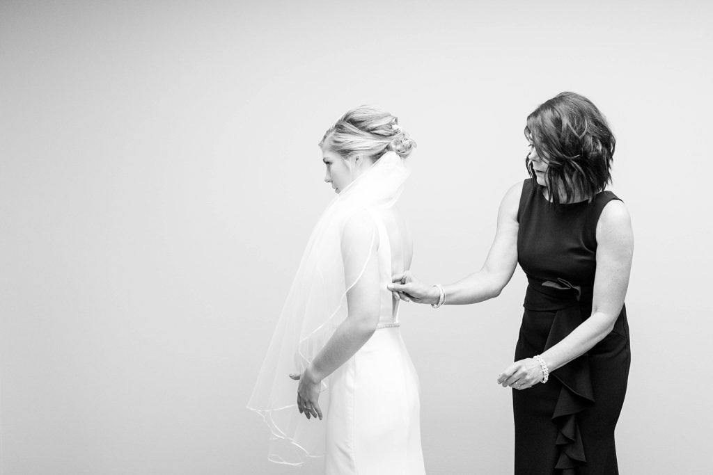 mother helps bride getting ready in a black and white photo in the church basement at St. Joseph Catholic church in Rice Lake, Wi