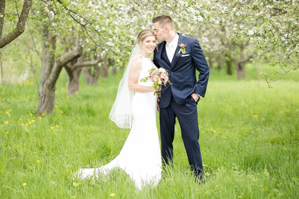 couple with groom kissing brides forehead in apple blossoms in Rice Lake, WI wedding