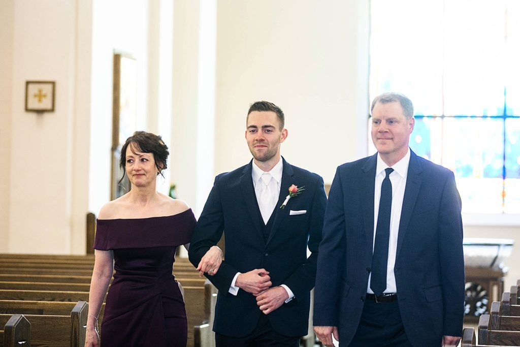 groom walking down the aisle with his parents at St. Joseph Catholic Church in Rice Lake,. WI