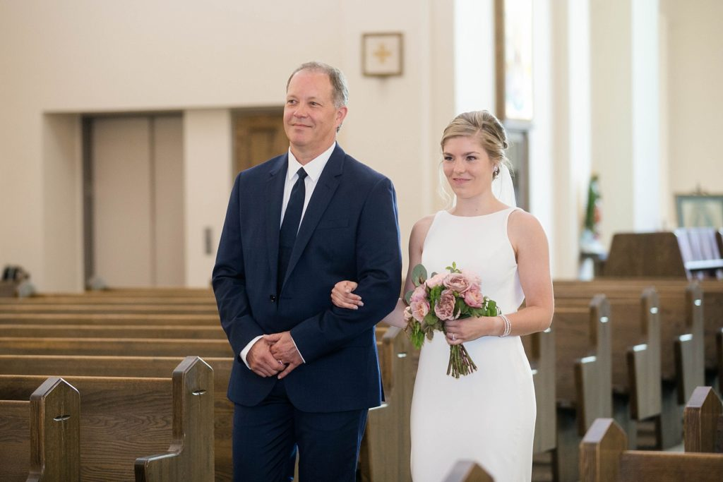 bride walking down the aisle with her father at her wedding at St. Joseph Catholic Church in Rice Lake,. WI