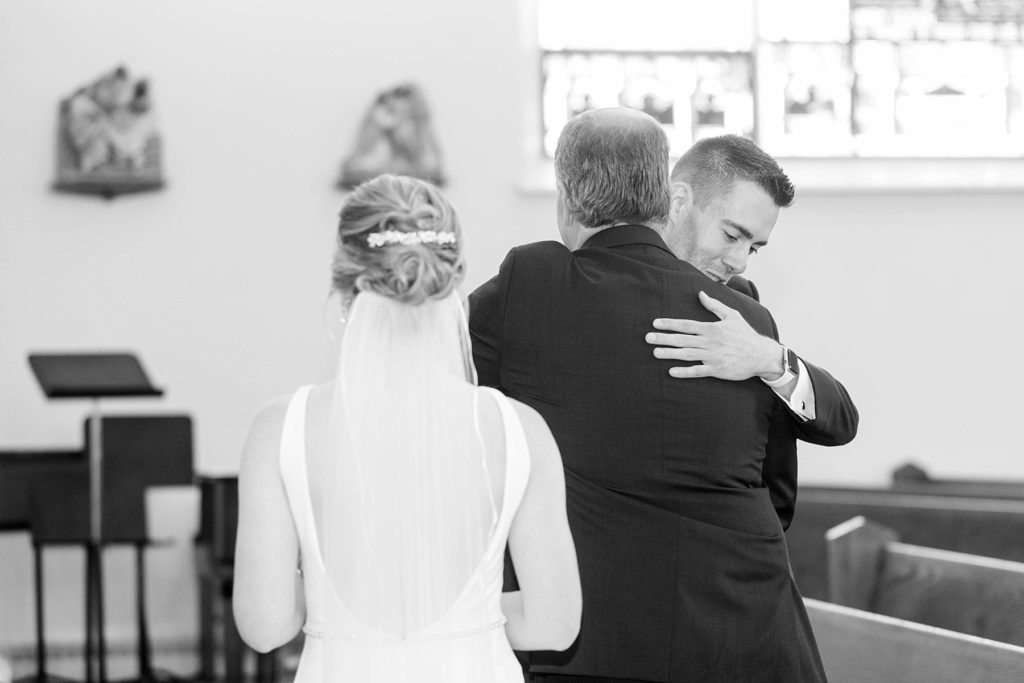 groom hugging the father of the bride and bride watching in a black and white photo at St. Joseph Catholic Church in Rice Lake,. WI