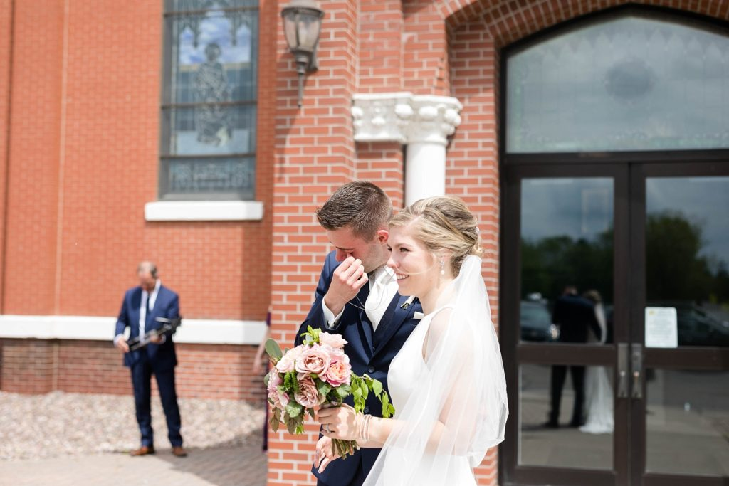couple outside at St. Joseph Catholic Church in Rice Lake,. WI waving to guests that couldn't come to the ceremony due to the Covid-19 pandemic