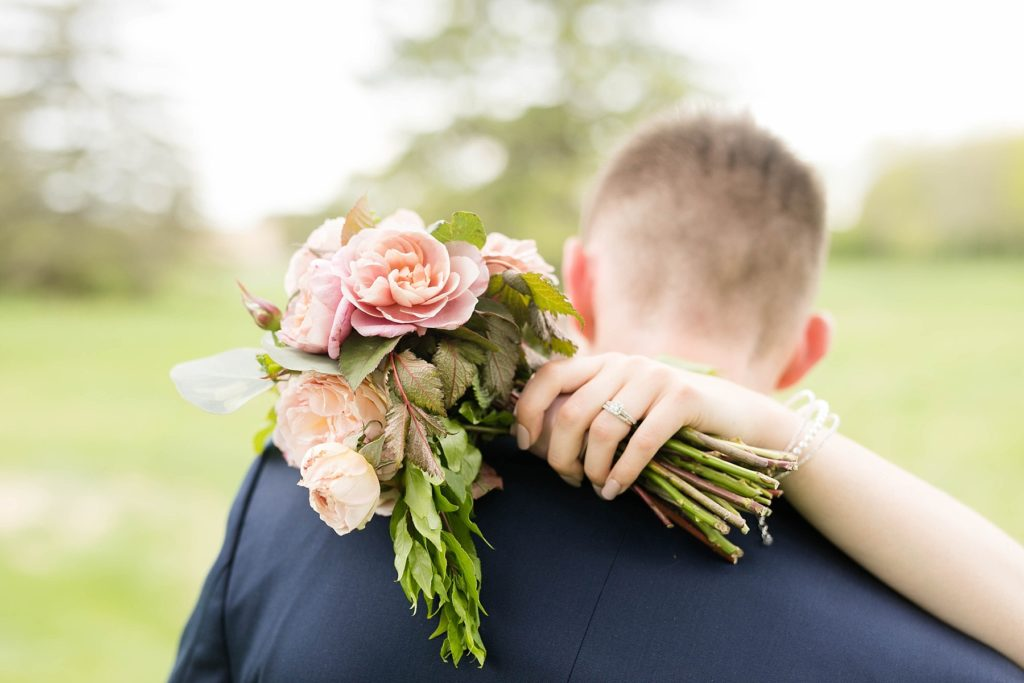 bouquet over grooms shoulder in brides hand in Rice Lake, WI at Turtleback Golf