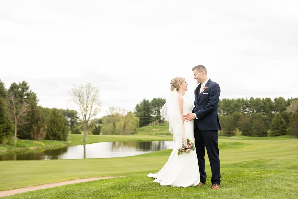 couple smiling at each other before their private first dance on hole #18 in Rice Lake, WI at Turtleback Golf