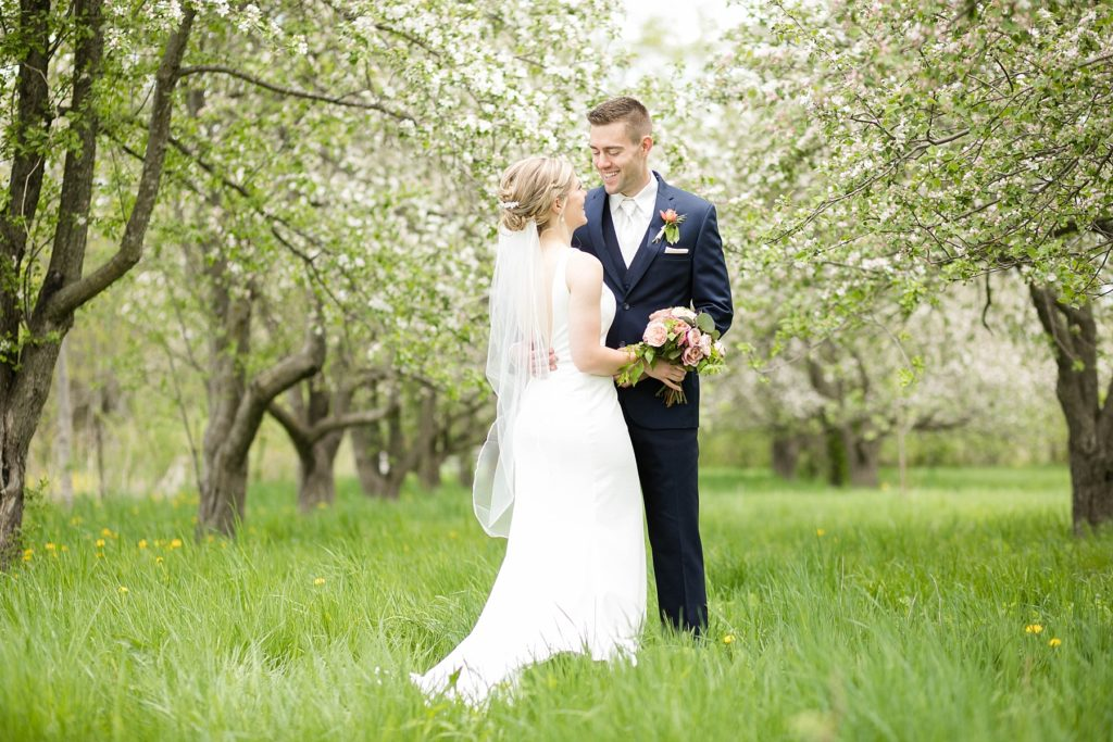 couple in blossomed apple trees for their wedding in Rice Lake, WI at St. Joseph Catholic church and Turtleback Golf